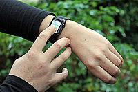 Person tippt auf Ihre Smartwatch am Handgelenk.