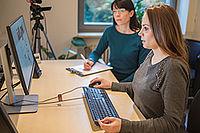Eine Dame sitzt vor einem PC und bedient die Maus, während sie von einer weiteren Dame beobachtet wird, die sich Notizen macht.